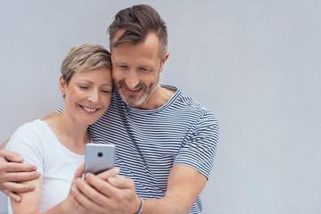 modernes, älteres paar schaut gemeinsam auf ein handy