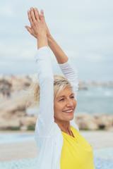 glückliche ältere frau am strand streckt entspannt die arme in die luft