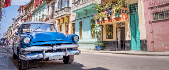 Poster Retro Vintage classic american car in a colorful street of Havana, Cuba. Panoramic travel photography.