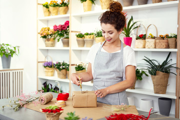 Skillful decorator. Nice pleasant woman wrapping a gift while working as a decorator