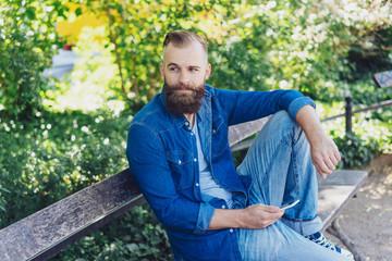 mann mit bart sitzt auf einer parkbank und hält sein handy in der hand