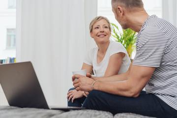paar sitzt mit dem laptop auf dem sofa und redet miteinander bei einer tasse kaffee