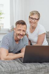 ehepaar sitzt zuhause auf dem sofa und surft im internet