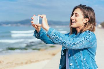lächelnde junge frau macht ein foto am strand