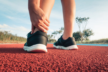 Close up portrait of sporty woman having ankle injury in running track, Healthcare and sport concept