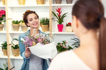 Perfect choice. Delighted nice woman offering a bouquet while looking at the customer