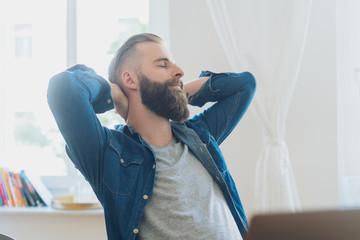 Mann entspannt zuhause und verschränkt die Arme hinter dem Kopf