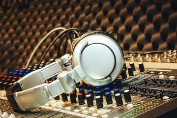 Close up instruments music background concept.DJ tools accessories headphones on sound mixer board in home recording studio.Free space for creative design text & wording mock up template wallpaper.