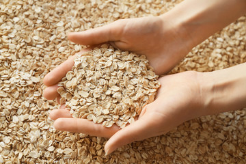 Woman with handful of raw oatmeal
