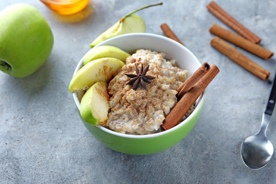 Bowl with tasty oatmeal, sliced apple and spices on grey textured background