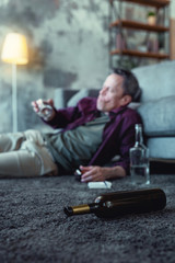 Addicted husband. Cheap cognac bottle lying near alcohol addicted husband after having emotional dispute with his wife