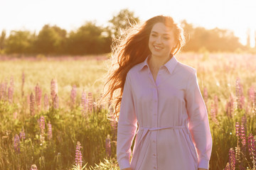 Close-up Fashion portrait of young pretty trendy woman with flying hair posing in flower field at sunset