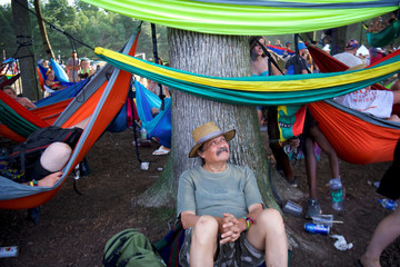 Jonny Johnson, 62, rests against a tree on the fourth and final day of the Firefly Music Festival in Dover, Delaware U.S.