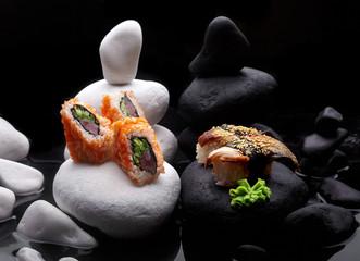 Close up of sushi nigiri with eel and sushi maki California set .Sushi. On dark stone with fog .Creative shot. Japanese athmophere.Copy space.Concept sushi maki versus nigiri.Ying and yang