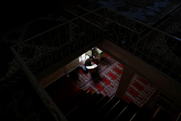 A man reads a Koran in a mosque in Silvan