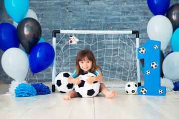 Little cheerful child dressed in sports clothes sitting on the floor near a football goal, looking at a big soccer ball. The first year, number one