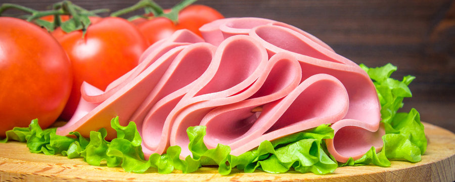 Sliced sausage with salad on a round wooden board. Banner
