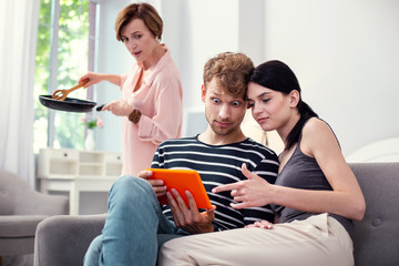 Young family. Pleasant young couple looking at the tablet screen while making purchases online