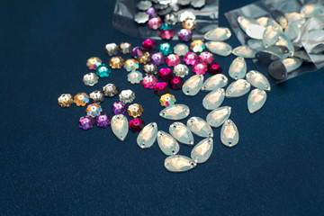 Scattering beads and glass leaves. Rhinestones embroidery. Beads on fabric. Materials for craft and creative work.