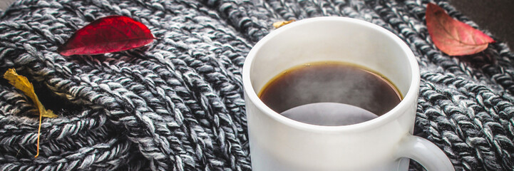 Mug of hot coffee in autumn setting on a wooden table with a knitted scarf, sweater. Comfort, warmth, cozy.. Banner