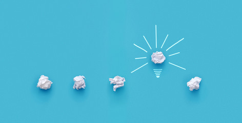 Great idea concept. Crumpled paper as a lightbulb isolated on blue background with copy space Fototapete