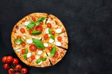 Hot italian pizza with tomatoes, basil and mozzarella on black stone background. Copy space for text