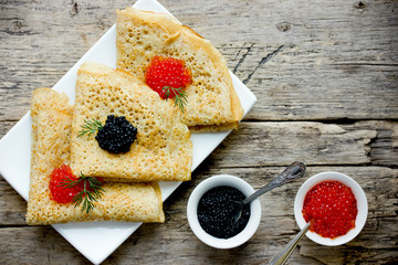 Thin yeast pancakes with red and black caviar, traditional dish of russian cuisine