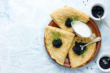 Pancakes with black caviar