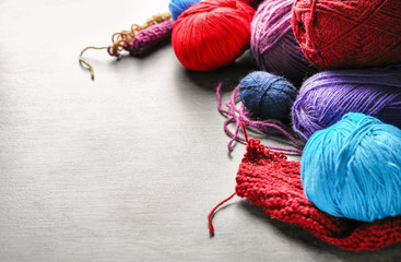 Colorful knitting yarn with unfinished clothes on table