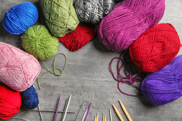 Colorful knitting yarn with needles on table