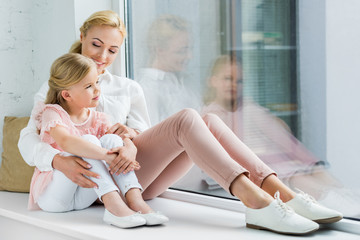 beautiful happy mother and daughter sitting together on windowsill