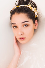 Close up portrait of sexy girl in a bath with milk