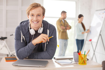 Favorite job. Gay male employee smiling to camera and holding pencil