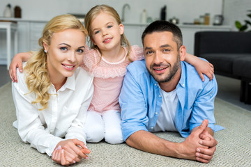 happy family with one child smiling at camera at home