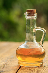 Apple vinegar in glass bottle on wooden boards with green natural background