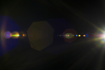 Solar camera lens flare light create hexagon of objective iris shapes of different colors depending on used antireflection coating of each lens surface on dark black background