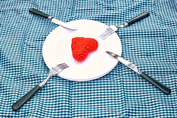 Table to the day of Saint Valentine - plate forks and red hearts on a plate.