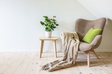 Beige armchair with a green pillow, blanket and a wooden table with a potted plant (Anthurium). Empty white wall in simple living room interior. Copy space