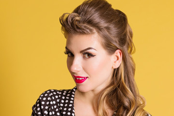 Beautiful woman with make up poses in yellow studio, pin up style