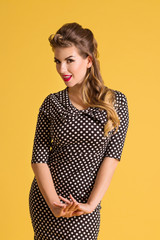 Pretty young woman in dress with hairdo stands in yellow studio, pin up style