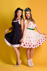 Two pretty women in dresses pose in yellow studio, pin up style, full body