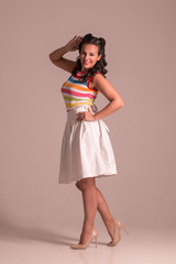 Pretty woman in skirt with hairdo poses in grey studio, pin up style, full body