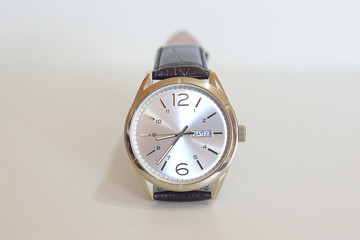 Modern fashionable male watch with golden details and leather strap displayed against a white background