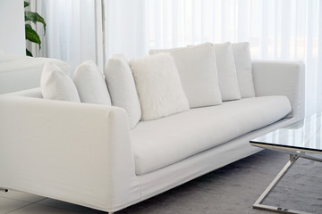 Interior of the living room of the hotel. Beautiful living room with white sofa. White Concept Living Room Interior. Modern bedroom interior in Luxury villa. White colours, big window