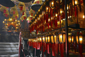 Incense burning with lanterns in dimly lit, traditional Temple in Hong Kong, China