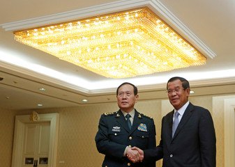 Chinese Defense Minister Wei Fenghe (L) shakes hands with Cambodia's Prime Minister Hun Sen before a meeting in Phnom Penh