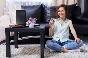 Girl sitting floor apartment smiling. Young woman wears casual clothes, jeans, blouse resting with crossed legs,holding glass water in her hand,looking camera. Happy female relaxing using laptop home.