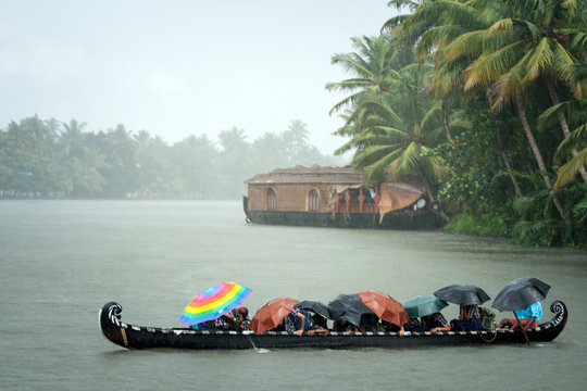 Monsoon time. People crossing a river by boat in rain
