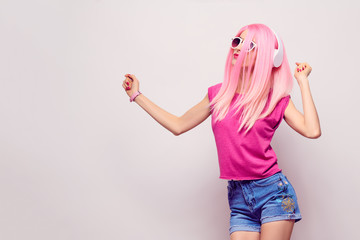 Wall Mural - DJ Girl Hipster with Pink Fashion Hairstyle Dance. Young Playful Model Woman in Trendy Headphones Smiling Having Fun. Music vibrations, Clubbing. Cool Party Style
