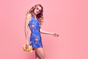 Wall Mural - Young Beautiful European girl Posing in Studio. Fashionable female Model, Wavy Hairstyle, Trendy Sunglasses. Gorgeous Woman in Stylish Glamour Summer Outfit.